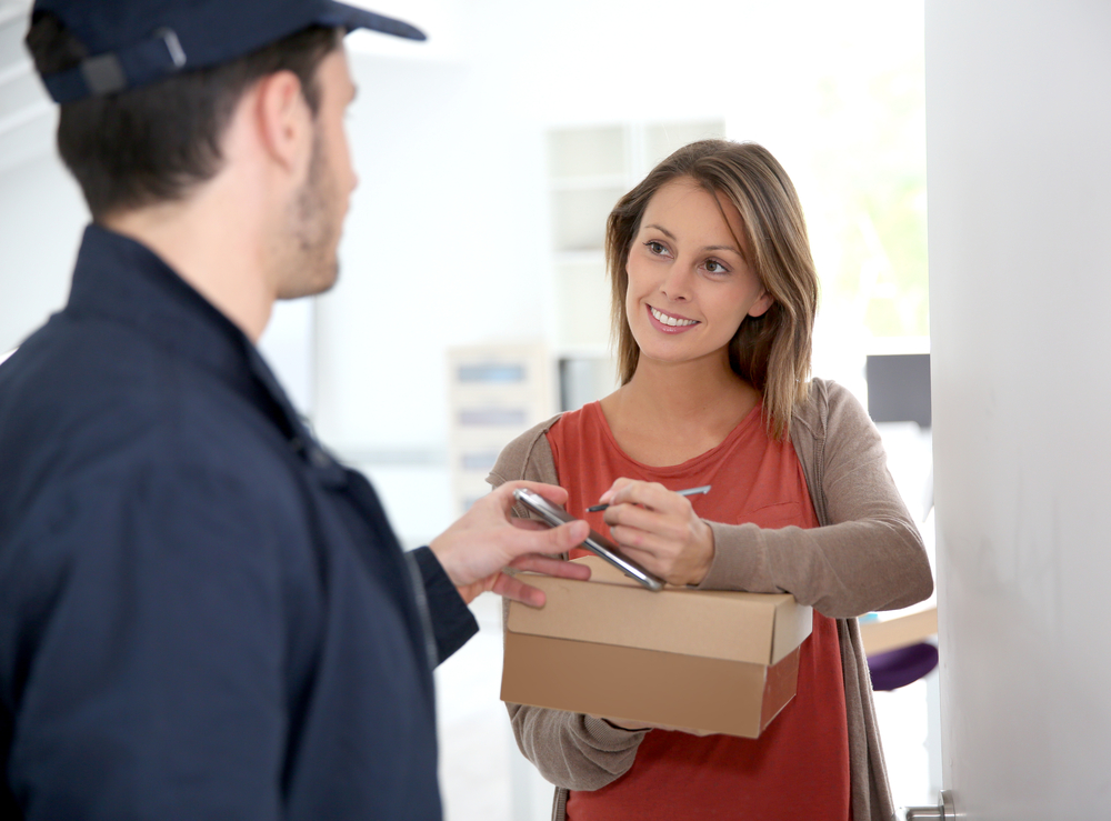 Woman signing LSO electronic receipt of delivered package